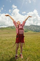 Italy, Seiseralm, Girl 8_9 in meadow cheering, arms up, portrait