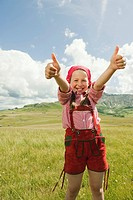 Italy, Seiseralm, Girl 8_9 in meadow giving thumbs up, smiling, portrait