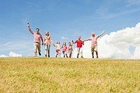 Italy, Seiseralm, Family walking in field, cheering