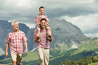 Italy, Seiseralm, Grandfather, Father and son 6_7 walking in meadow, smiling, portrait