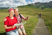 Italy, Seiseralm, Senior couple holding map, smiling, portrait