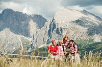 Italy, Seiseralm, Four persons looking at map, portrait