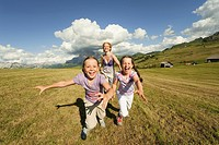 Italy, Seiseralm, Mother and daughters 6_7, 8_9 running in meadow, laughing, portrait