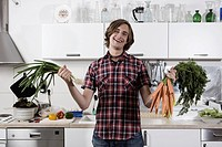 Germany, Berlin, Young man in kitchen holding bunch of carrots and spring onions, laughing, portrait