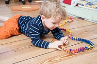 Germany, Berlin, Boy 3_4 lying on floor, playing with streamer