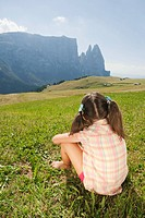Italy, South Tyrol, Seiseralm, Girl 6_7 sitting in meadow, rear view