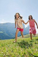 Italy, South Tyrol, Seiseralm, Two girls 6_7 10_11 running in field