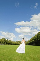 Germany, Bavaria, Bride walking in park, rear view