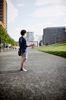 Germany, Berlin, Young man holding city map