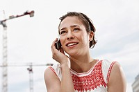 Germany, Berlin, Young woman using mobile phone, portrait, close_up