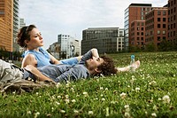 Germany, Berlin, Young couple lying in meadow, high rise buildings in background