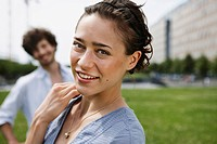 Germany, Berlin, Young woman, man in background, portrait, close_up