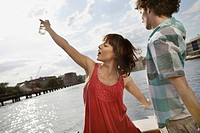 Germany, Berlin, Young couple on motor boat, woman dancing
