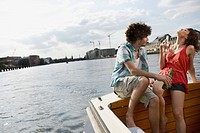 Germany, Berlin, Young couple on motor boat holding bottles, portrait