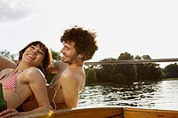 Germany, Berlin, Young couple on motor boat, man wearing headphones, portrait, close_up