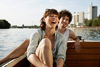 Germany, Berlin, Young couple on motor boat, laughing, portrait