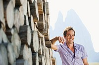 Italy, South Tyrol, Seiseralm, Man standing next pile of wood