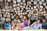 Italy, South Tyrol, Family resting in front of pile of wood