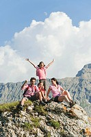 Italy, South Tyrol, Family sitting on rock, cheering, portrait
