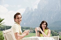 Italy, South Tyrol, Seiseralm, Couple in cafe holding coffee cups