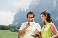 Italy, South Tyrol, Seiseralm, Couple holding coffee cups, outdoors