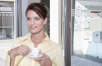 Germany, Cologne, Businesswoman in office taking a break, drinking coffee