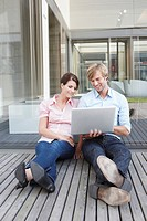 Germany, Cologne, Two business people sitting on floor using laptop