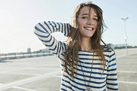 Germany, Berlin, Young woman smiling at empty parking lot, portrait