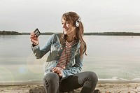 Germany, Berlin, Lake Wannsee, Woman looking at cassette tape, using headphones