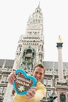 Germany, Bavaria, Munich, Marienplatz, Man holding gingerbread heart, smiling, portrait
