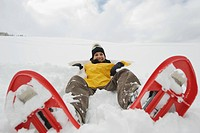 Italy, South Tyrol, Young woman with snowshoes lying in snow