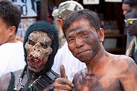 Portrait of two men, one masked, the other with soot smeared on his face during the Ati_Atihan Festival, an annual feast in honour of the Santo Nino, ...