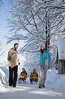 Germany, Bavaria, Parents pulling children on sleds
