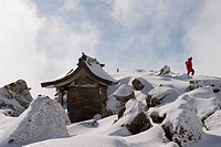 Shrine and climber on snow covered Iwaki San mountain, Aomori prefecture, Japan, Asia