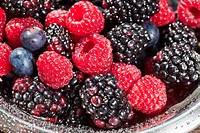 Fresh berries with water droplets in bowl, close_up