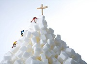 Plastic figurines climbing a mountain