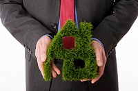 Person holding house symbol made from grass, close_up