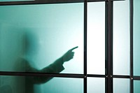 Germany, Munich, Silhouette of businessman behind frosted glass, gesturing