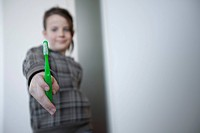 Girl 8_9 holding toothbrush, portrait