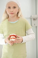 Germany, Bavaria, Landsberg, Girl 8_9 holding model of teeth, portrait