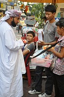 Bangkok (Thailand), a Muslim man buying souvenirs at 'Soi Arab', near Sukhumvit Road
