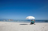 Man lying with hands on head - under umbrella - on Clifton 4th beach - cape Town