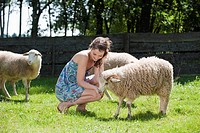 Germany, Bavaria, Young woman feeding sheep, portrait