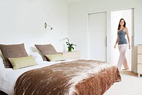 Woman walking through bedroom