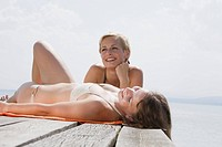 Germany, Bavaria, Two young women lying on jetty, smiling, portrait