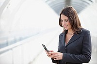 Germany, Bavaria, Munich, Businesswoman using mobile phone at airport, portrait