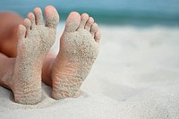 Italy, Sardinia, Person lying on beach, sandy feet