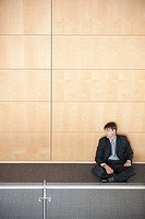 Businessman sitting in corridor