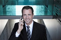 Germany, Cologne, Businessman using mobile phone, smiling, portrait