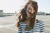 Germany, Berlin, Young woman smiling at empty parking lot with the wind blowing her hair